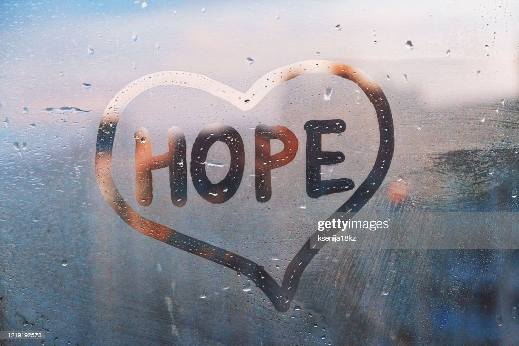 Foggy glass on window with written finger word yellow color Hope in paint heart concept photo with copy space on blue and warm background : Stock Photo