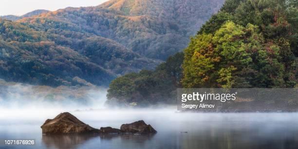 foggy morning at hibara lake and colours of early autumn in japan - flanco de valle fotografías e imágenes de stock