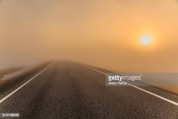 Foggy road at sunrise in the mountains