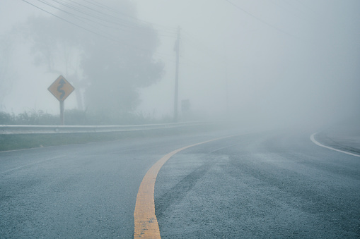 foggy rural asphalt highway perspective with white line, misty road, Road with traffic and heavy fog, bad weather driving 1055906130