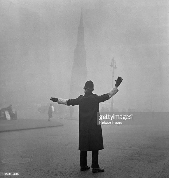 Foggy scene on the Strand London circa 1946circa 1959 A City of London traffic policeman outside the Charing Cross Hotel using outstretched arms to...