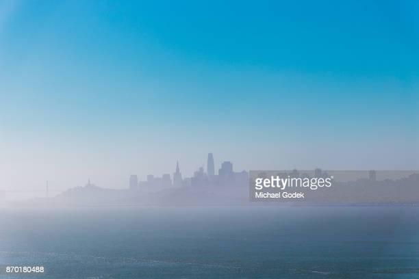 Foggy skyline of San Fransisco against blue sky