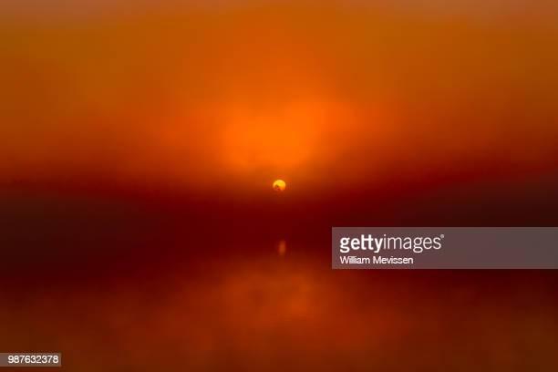 foggy sunrise 'red' - william mevissen stockfoto's en -beelden