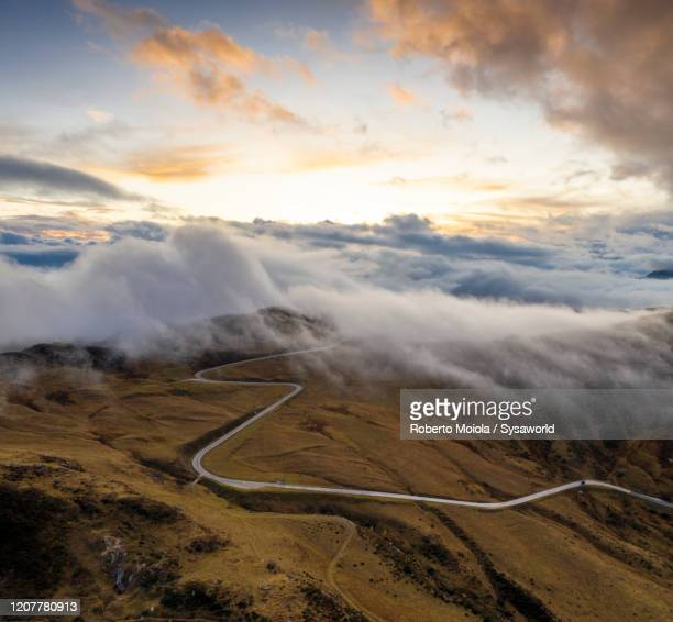 foggy sunset over giau pass, aerial view, dolomites, italy - mountain pass stock pictures, royalty-free photos & images