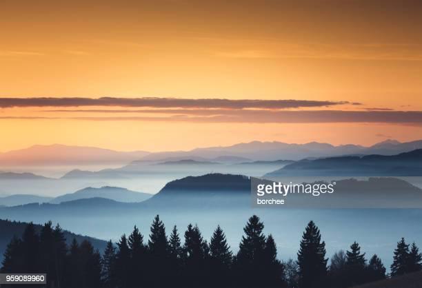 brouillard au coucher du soleil - couches superposées photos et images de collection