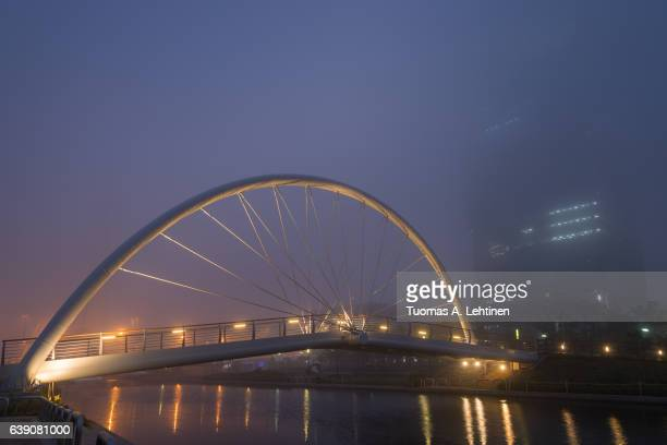 foggy view of a river, lit bridge and skyscraper in incheon, south korea in the evening. - songdo ibd stock pictures, royalty-free photos & images