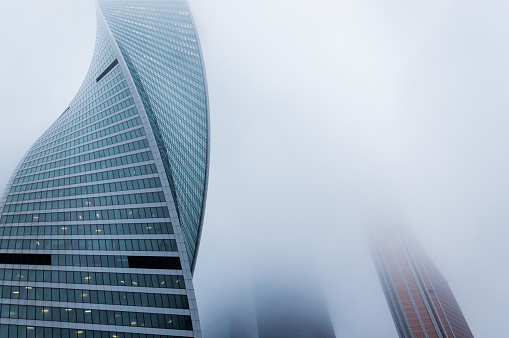 Foggy weather in Moscow, capital city of Russia.Front view of the modern glass twirly skyscraper outgoing to the foggy sky - gettyimageskorea