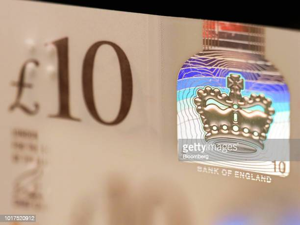 A foil patch containing an image of the coronation crown sits on the British 10pound banknote stands in this arranged photograph in London UK on...