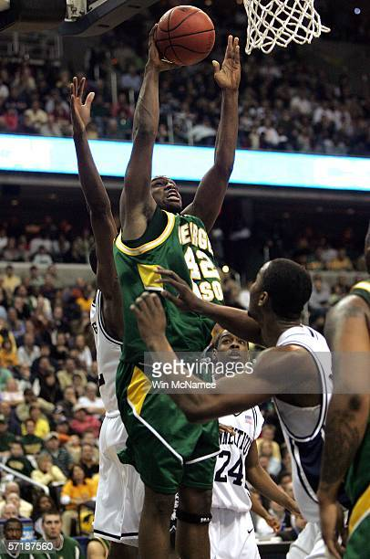 Folarin Campbell of the George Mason Patriots lshoots over the defense of the Connecticut Huskies during the Regional Finals of the NCAA Men's...