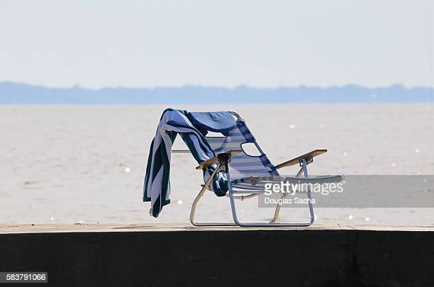 foldable lounge chair and beach towel on a pier - foldable stock pictures, royalty-free photos & images