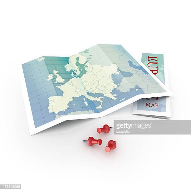 A foldable map of Europe laid open with three red push pins