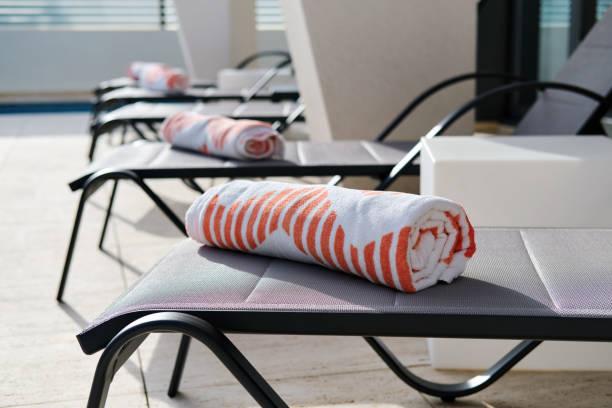 Folded beach towels on sunbeds in summer terrace