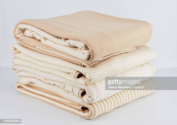 folded blanket against white background - bedclothes stock pictures, royalty-free photos & images