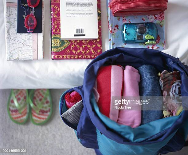 folded clothes in open rucksack, beside belongings piled neatly on bed - open backpack stock pictures, royalty-free photos & images