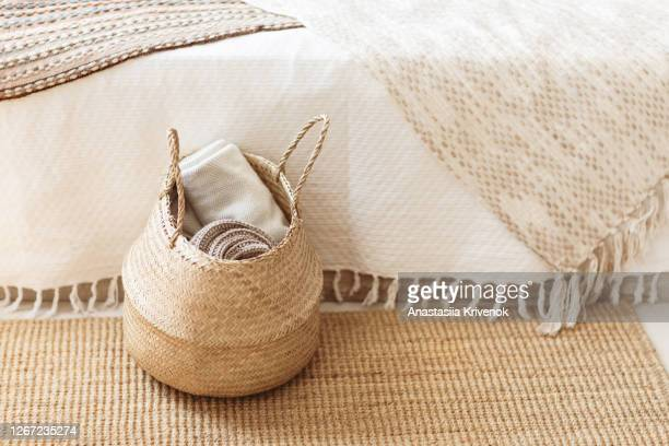 folded gray knitted plaid in straw basket on wicker carpet near bed. cozy hygge home style. fall winter season concept. close up, copy space. - wicker stock pictures, royalty-free photos & images