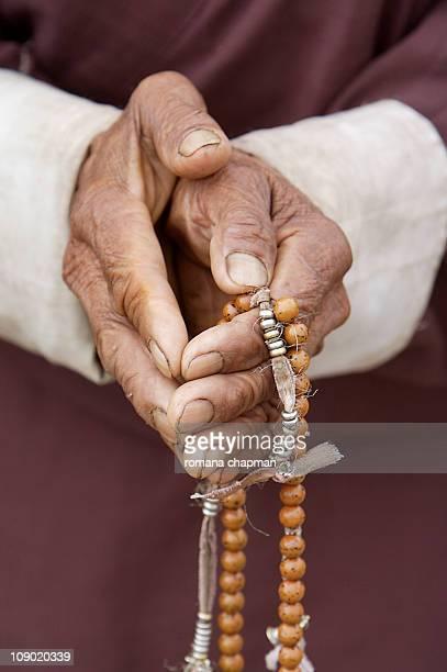 folded hands and prayer beads - dochula pass stock-fotos und bilder
