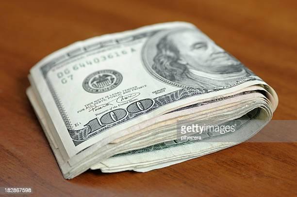 Folded Hundred Dollar Bills on a Wooden Table