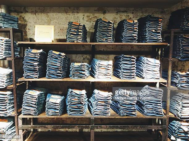folded jeans kept on shelves in shop - jeans stock photos and pictures