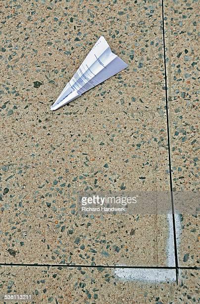 Folded paper airplane on sidewalk