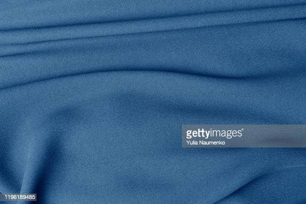 folded piece of blue fabric, folds of fabric. beautiful texture of blue color. a piece of fabric for a seamstress cut. - silk stock pictures, royalty-free photos & images