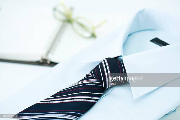 Folded shirt and tie, glasses on notebook in background, high angle view, close up, Japan