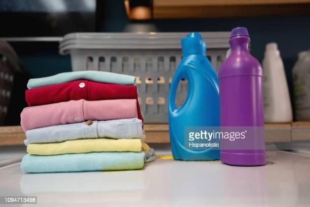 gefaltete hemden auf waschmaschine neben wäsche-produkte - weichspüler stock-fotos und bilder