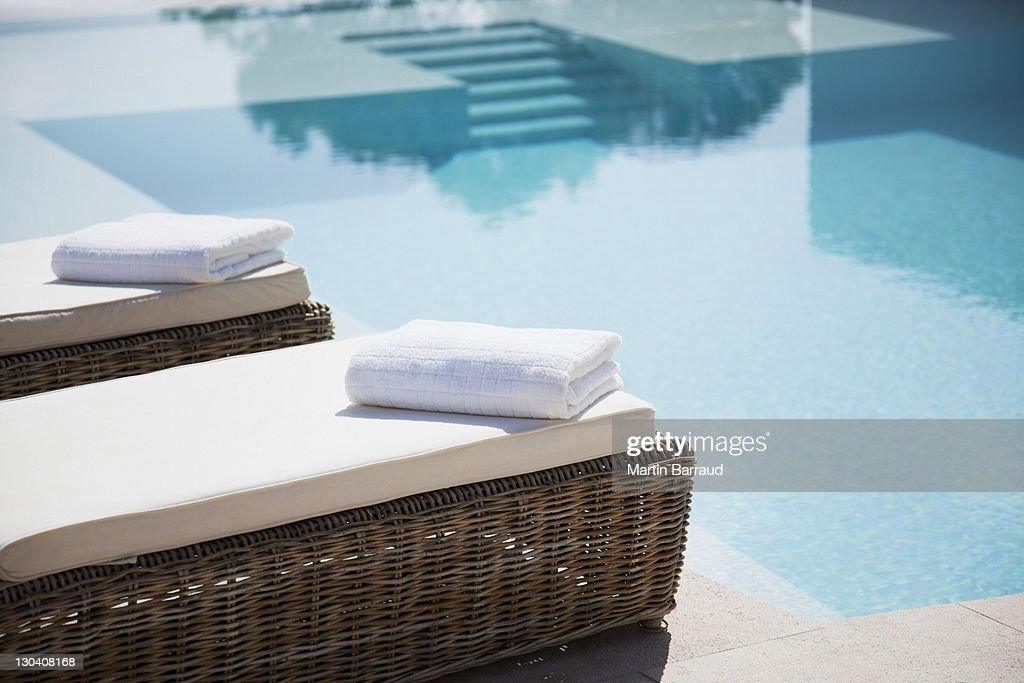 Folded towels on lounge chairs beside pool : Stock Photo