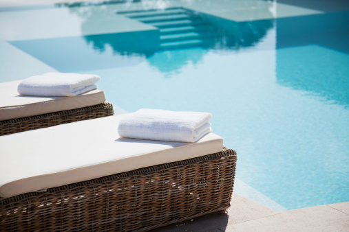 Folded towels on lounge chairs beside pool 130408168