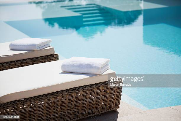 folded towels on lounge chairs beside pool - poolside stock pictures, royalty-free photos & images