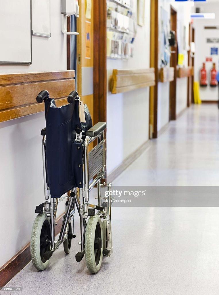 Folded wheelchair in hallway of hospital : Stock Photo