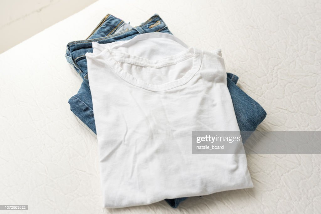 Folded white t-shirt and jeans on edge of bed from above : Stock Photo