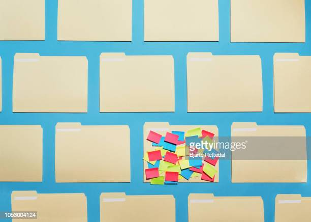 folder in a grid of plain folders with a lot of colourful sticky notes - bjarte rettedal stock pictures, royalty-free photos & images
