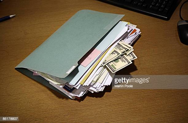 folder on desk with 100 dollars bills stuck in it