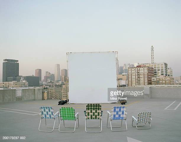 Folding chairs sitting in front of projection screen on rooftop