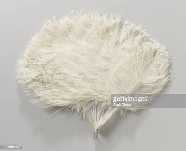 Folding fan of white ostrich feathers on a closed raw motherofpearl frame raw motherofpearl frame The frame has 16 connected legs with a metal...