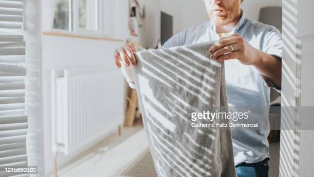 folding laundry - husband stock-fotos und bilder