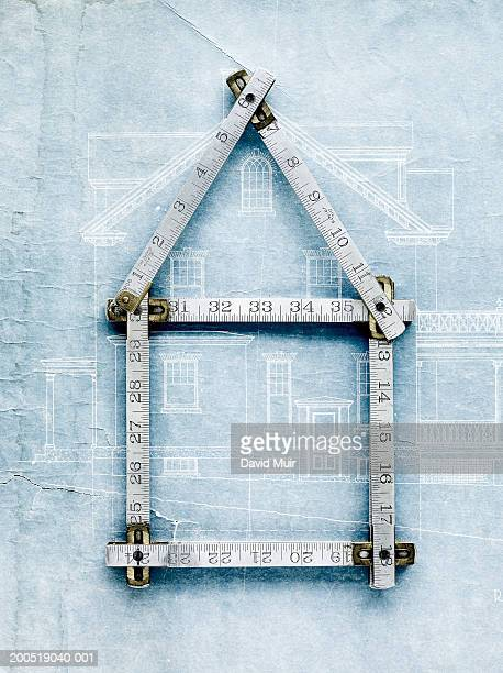 Folding ruler in the shape of house on blue prints, close-up