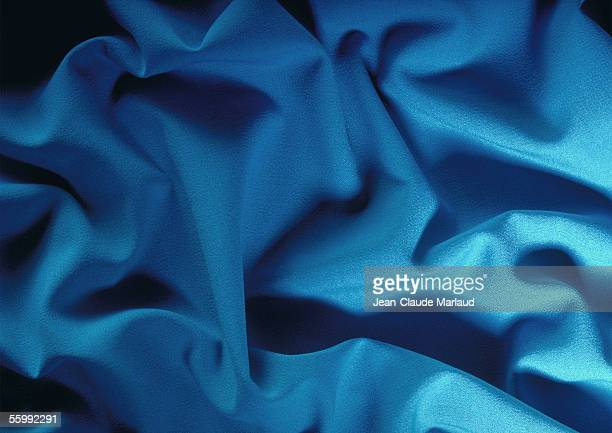Folds in blue fabric, close-up, full frame
