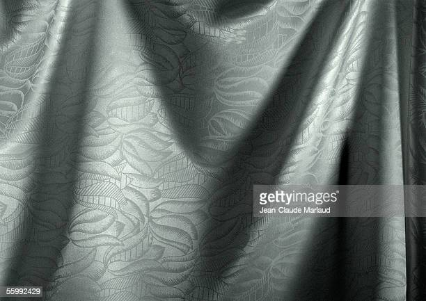 Folds in silver fabric with floral pattern, close-up, full frame