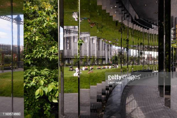 Foliage is seen behind mirrored panels as people enjoy the sunshine at Gasholder Park on July 22 2019 in London England On July 22 London officially...