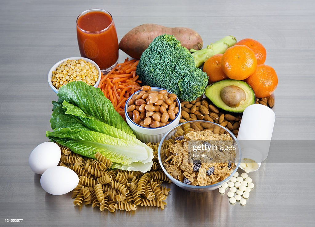 Folic Acid supplement and foods on stainless kitchen counter : Stock Photo