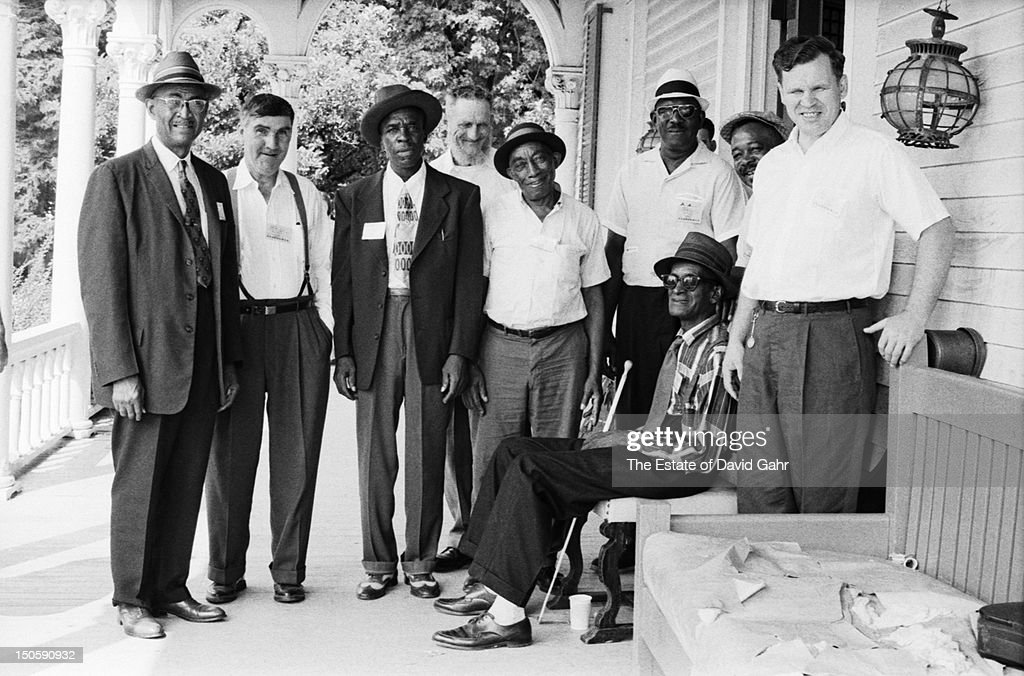 Folk and blues greats pose for a portrait in July, 1964 at the Newport Folk Festival in Newport, Rhode Island. L-R: guitarist and singer Reverend Robert Wilkins, old-time musician Gaither Carlton, blues singer and guitarist Skip James, folk musician Arnold Watson, blues guitarist and singer Mississippi John Hurt, blues musician Yank Rachell, blues guitarist and singer Sleepy John Estes, blues musician Hammie Nixon, folk and bluegrass guitarist and singer Doc Watson.