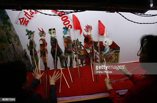Folk artists perform a shadow play themed 'Five Fuwas Usher The Olympics' to mark the upcoming 100-day-countdown to the Beijing Olympic Games on...