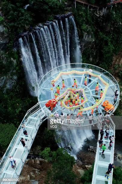 Folk artists perform dragon dance on a glassbottomed bridge at the Gulongxia scenic spot on July 1 2018 in Qingyuan Guangdong Province of China A...