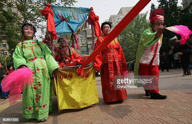 Folk artists perform during the 'Xiaochehui' show held at a community to mark the upcoming 100-day-countdown to the Beijing Olympic Games on April...