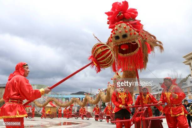 Folk artists push forward the 45metrelong straw dragon with 13 red wheelbarrows while performing Baijiang Straw Dragon Dance to welcome the Lantern...