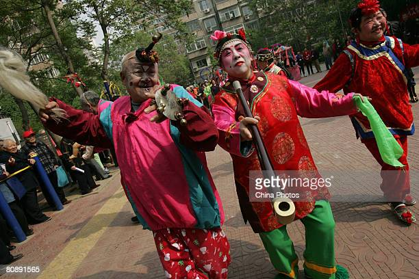 Folk artists who act as a dull and his wife perform during the 'Xiaochehui' show held at a community to mark the upcoming 100-day-countdown to the...