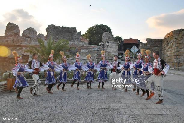 a folk dance group poses for pictures in traditional costumes. - medieval shoes stock pictures, royalty-free photos & images