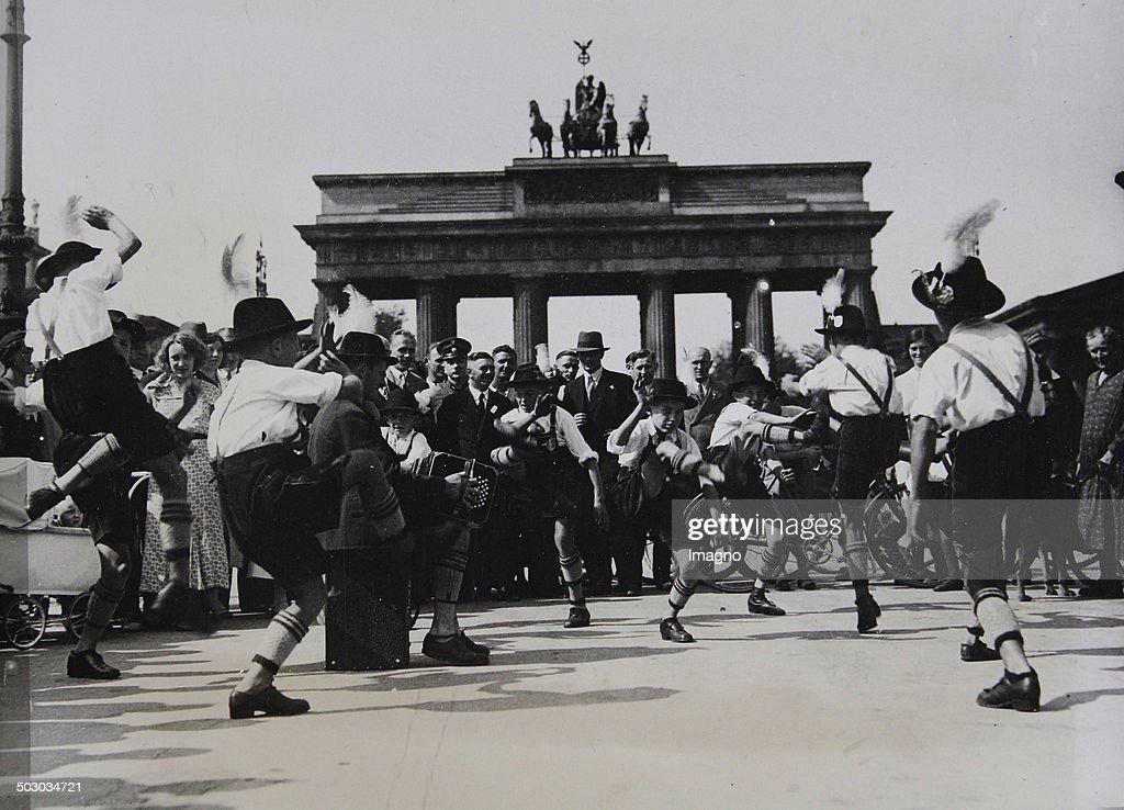 A folk dance performance of a Bavarian group of so-called Schuhplattler from the Upper Bavarian village Siegsdorf at the Brandenburger Gate. Berlin. About 1935. Photograph.