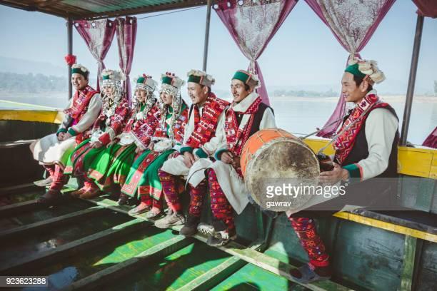 Folk musician and dancers of kinnaur riding in a boat.